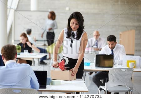 Businesswoman In Office Preparing Package For Shipping