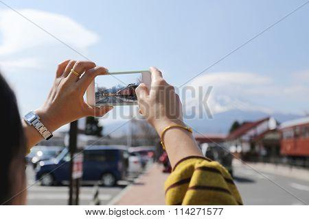 The Image Of Mount Fuji And Kawaguchiko Station On A Smartphone Screen.