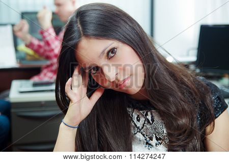 Hispanic brunette office worker sitting by desk resting tilted head in hands looking tired