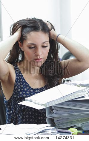 Hispanic brunette office woman sitting by desk with paper file archive open. holding her head lookin