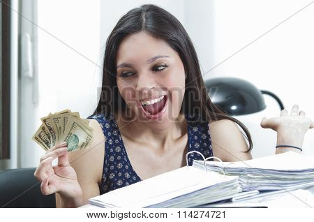 Hispanic brunette office woman sitting by desk with paper files archive open and holding several ten