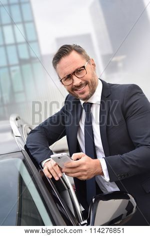 Taxi driver standing by car outside and using smartphone