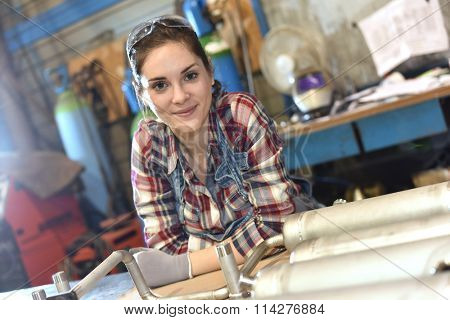 Woman with protective glasses working in metallurgy workshop