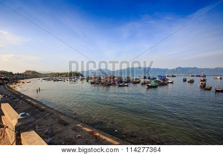 Distant Group Of Vietnamese Fishing Boats Against Hilly Islands