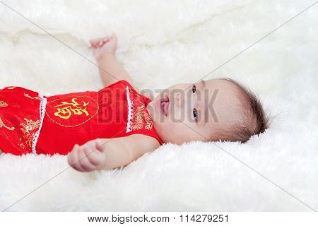 Cute five months asian baby smiling in red cheongsam. on bright soft carpet