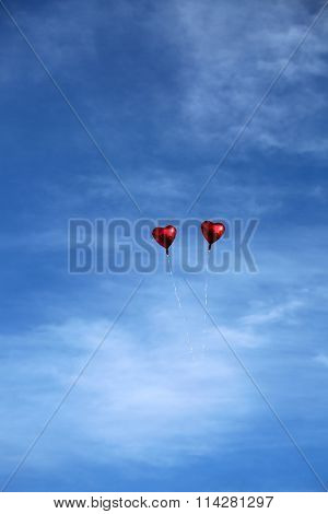 Red Mylar Heart Shaped Valentines Day Helium Filled Balloon floats freely into the Blue Sky with White Clouds. Valentines Day is celebrated on February 14 of each year.