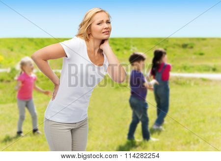 woman suffering from backache over group of kids