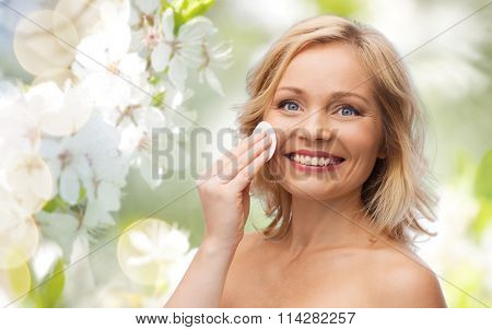 happy woman cleaning face with cotton pad