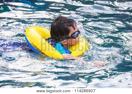Funny Asian Boy With Swim Tube In Pool. Outdoor.