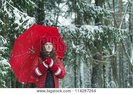 Winter outdoors portrait of cheerful woman in warm clothes wearing tuque and long arm warmers during