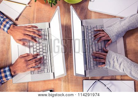 Overhead view of hands typing on laptop keyboard at desk in creative office