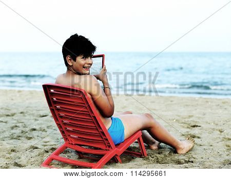 Young Boy Reads An Ebook On Red Chairs