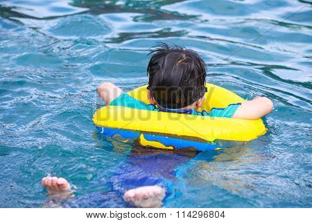 Back View Of Asian Boy With Swim Tube In Pool. Outdoor.
