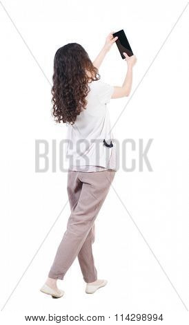 back side view of woman walking with a tablet PC is in the hands of beautiful curly girl in motion.  back side view of woman walking with a tablet PC is in the hands of beautiful curly girl in motion