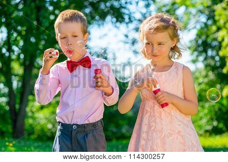 Children 6 Years Old Doing Soap Bubbles In The Park