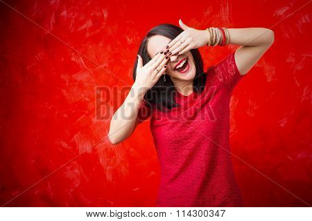 Happy woman covering her eyes with both hands