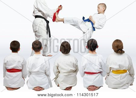 Sportsmen sitting in pose looking at demonstration punch karate