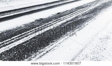 Black Asphalt Pavement Under Fresh Snow Layer