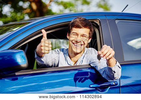 Close up of young happy hispanic man wearing glasses holding out car keys, showing thumb up hand gesture and smiling through car window - new drivers concept