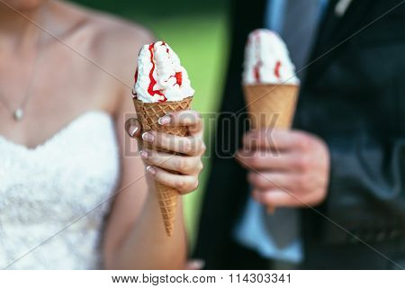 Bride And Groom Holding Icecream In Their Hands On Wedding Day