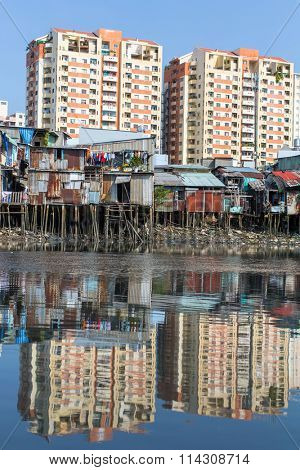 Views of the city's Slums from the river (in the background and in the water reflection of the new high-rise buildings) Ho Chi Minh City, Vietnam.