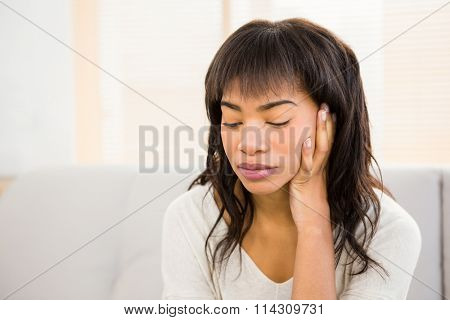 Stressed woman holding her head on couch at home