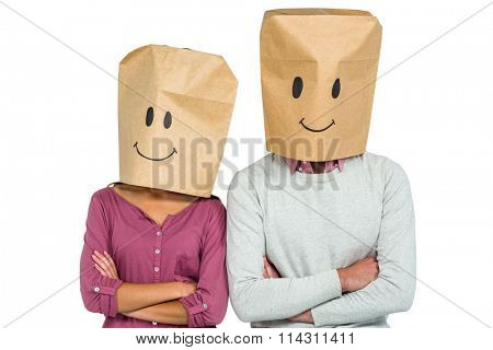 Couple covering their faces with paper bag with arms crossed on white screen