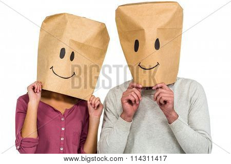 Couple covering their faces with paper bag on white background