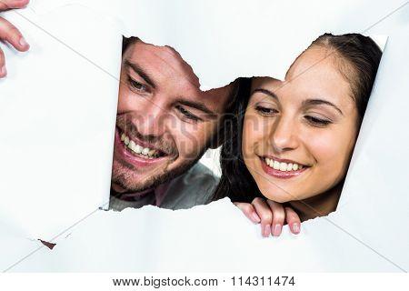 Close-up of smiling couple peeking through torn paper