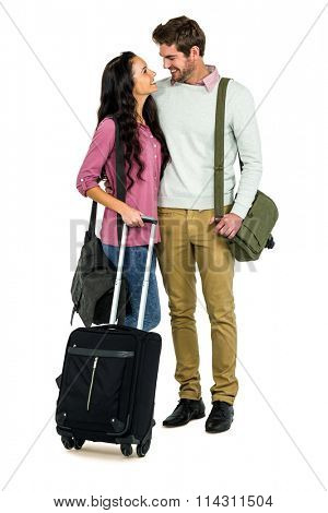 Smiling couple with luggage on white background
