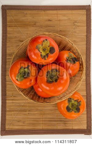 Some Khaki Fruits Over A Wooden Surface