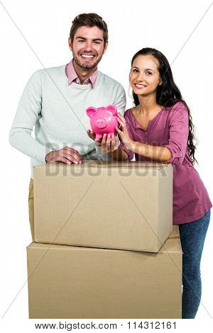 Smiling couple holding on boxes with piggy saver on white screen