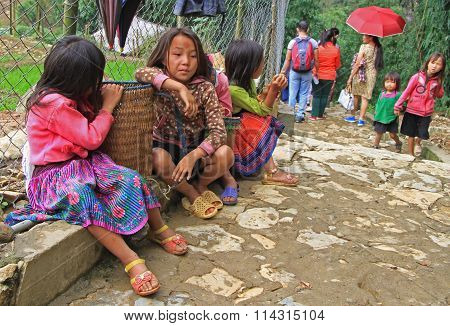 girl are sitting at the tourist pathway in village CatCat, Vietnam