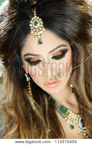 Beautiful female model in traditional indian bride costume with makeup and jewellery
