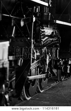 Closeup of heavy steam train on tracks, black and white