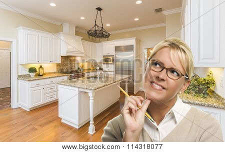 Attractive Daydreaming Woman with Pencil Inside Beautiful Custom Kitchen.