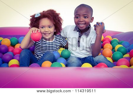 Cute children in ball pool holding balls on white screen