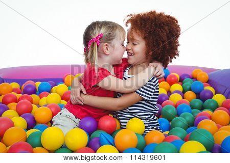 Cute smiling girls in sponge ball pool hugging