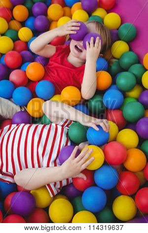 Cute smiling kids in sponge ball pool covering eyes with balls