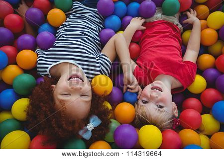 Cute smiling girls in sponge ball pool looking at the camera