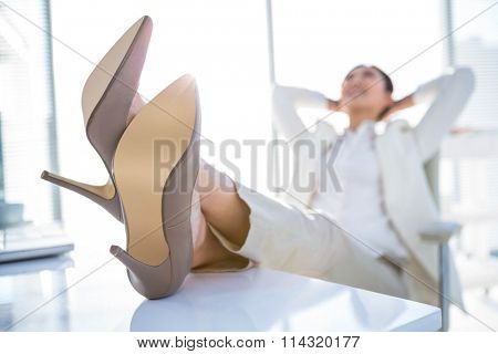 Relaxed businesswoman sitting with her feet up at desk
