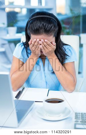 Worried businesswoman covering her face at her desk