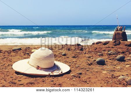 Holiday concept with hat and sandcastle on the seaside. Toned