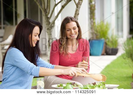 Couple Of Female Friends Sitting Outdoors Eating Lunch