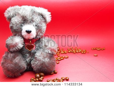 A valentine prop, black teddy bear with red heart on neck and chocolates on floor