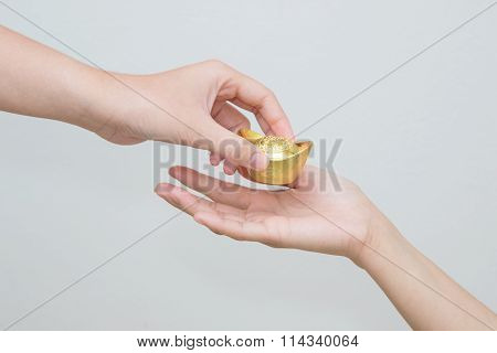 Hand Giveing Gold Ingot To Someone For Chinese New Year Celebration