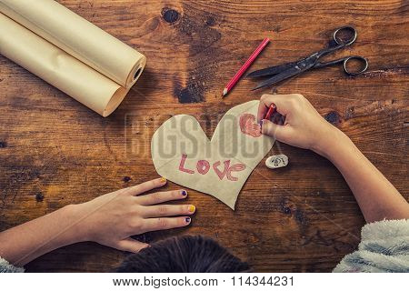 Young girl draws love text on handmade paper hearts. Valentines text on paper heart