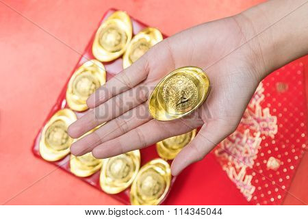 Hand Giveing Gold Ingot For Chinese New Year Celebration On Red Background
