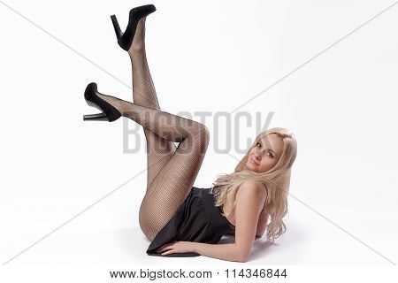 Blonde Woman Lying In Short Black Dress And Pantyhose