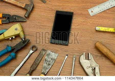 different old tools with smart phone on wood